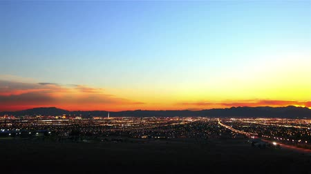 казино : A sped up panoramic view of all of las vegas and the mountains behind las vegas at sunset. The video starts in the evening and ends at night.