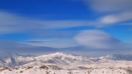 скат : Time-lapse shot of snow-capped mountains in Utah. This shot was taken during the day and clouds are seen moving through the sky at this time.