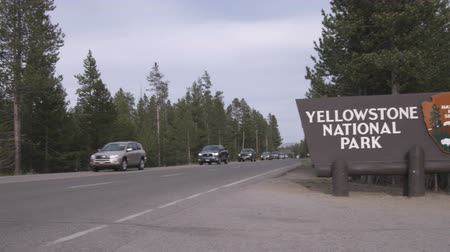 дорожный знак : Wide shot of road with cars and Yellowstone sign Стоковые видеозаписи