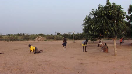 solo : Wide shot of kids playing ball on dirt ground