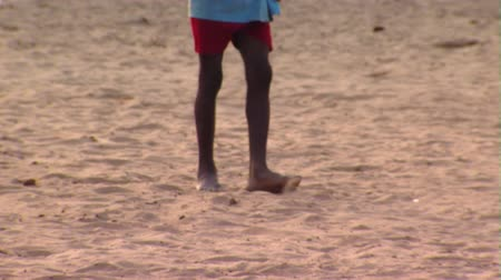 black dirt : Close up shot of kids playing ball on dirt ground