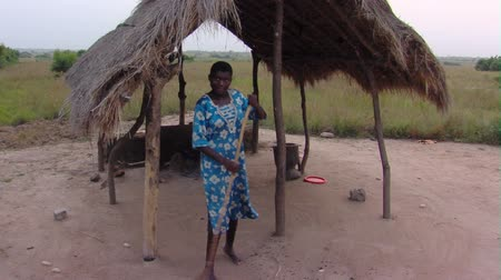 chata : Wide shot of woman cleaning hut