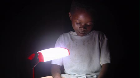 bída : Medium shot of child reading by lamp