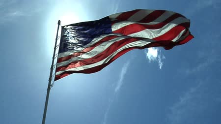 amerika : An American flag waves from a flagpole backlit by a blinding sun in a blue sky with wisps of white clouds.