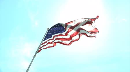 allegiance : Looking up at an American flag flying in slow motion against a turquoise sky. Stock Footage