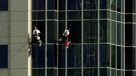 cleaner : Two maintenance men wash windows in unison while hanging from the side of a skyscraper on a sunny day in Salt Lake City, Utah.