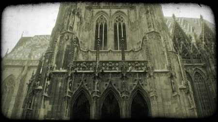 řemeslníci : Tilt down on exterior of St. Stephens Cathedral, showing intricate gothic design of tall front and side walls, onto street below where people walk by. Vintage stylized video clip.