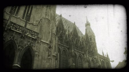 víry : Tilt up on exterior of St. Stephens Cathedral, showing intricate gothic design of tall front and side walls, onto street below where people walk by. Vintage stylized video clip. Dostupné videozáznamy