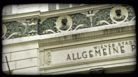 bronz : Allgemeine Poliklinik, School of Psychology - Logotherapy, Vienna Austria sign in front of building with bronze faces lined along panel of building. Vintage stylized video clip.