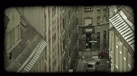 verim : Medium shot above  tall European stylized apartment buildings, facing each other above narrow street with cars and a person walking in Vienna, Austria. Vintage stylized video clip. Stok Video