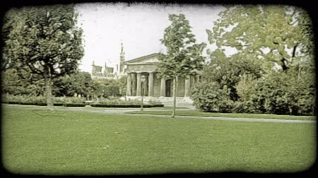 struktura : A shot of a garden in Vienna and an ancient structure with people passing. Vintage stylized video clip.