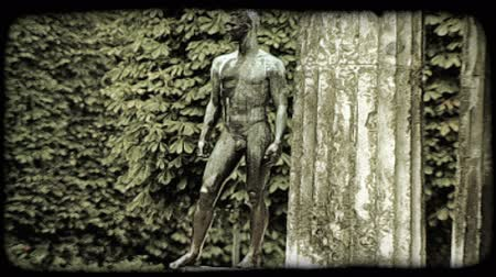 struktura : A tilt up shot of a statue in front of a large structure in a Vienna garden. Vintage stylized video clip. Wideo