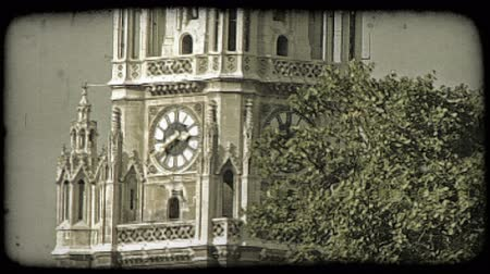 náboženství : A tilting shot of a Vienna cathedrals steeple behind some trees. Vintage stylized video clip.