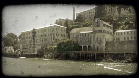 letectví : Pan view from boat of famous, old Alcatraz station and buildings near San Fransisco bay in California. Vintage stylized video clip. Dostupné videozáznamy