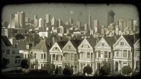 artsy : Famous Alamo Square row of townhouses in San Fransisco with green manicured park and trees in foreground and busy San Fransisco downtown towering up in background. Vintage stylized video clip. Stock Footage