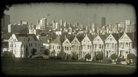artsy : Zoom toward famous Alamo Square row of townhouses in San Fransisco with green manicured park and trees in foreground and busy San Fransisco downtown, with Trans America building in center, towering above in background. Vintage stylized video clip. Stock Footage