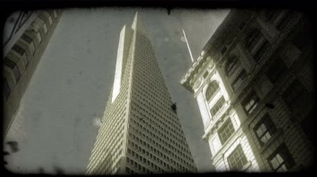 régi : Low-angle pan of TransAmerica Tower surrounded on both sides by other tall San Fransisco buildings, with blue sky as backgroung. Vintage stylized video clip.