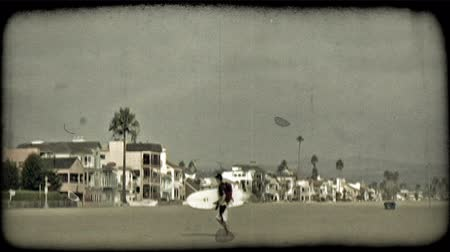 сбор винограда : Young man surfer carrying surf board, walks along sandy Southern California beach with houses, condos and beach rentals in background under overcast sky. Vintage stylized video clip.
