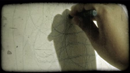 criar : Close-up on childs hand as he draws circular scribbles with a blue crayon onto a white canvas. Vintage stylized video clip. Vídeos