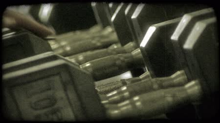 súlyzó : Close-up of tightly stacked row of barbell weights for body builders to do curls with in a fitness gym.  Hands reach in to replace weights. Vintage stylized video clip.