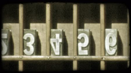 régi : Pan of metal letter and number blocks in compartments of a wooden shelf, upside down and ready to be used in the printing press. Vintage stylized video clip.