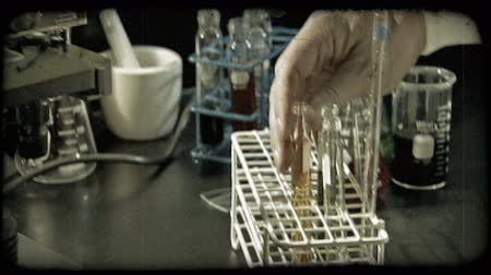 prova : Man puts beakers filled with colored liquid into sorting rack while camera pans over and up to microscope in lab. Vintage stylized video clip.