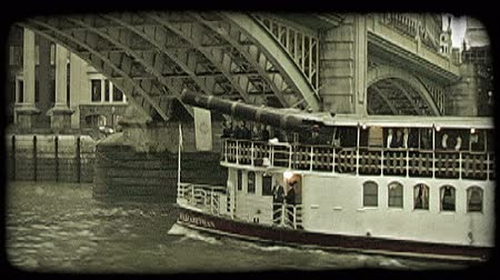 kültürlü : Large tour vessel boat , with conversing gentlement on bottom level, draws near a historic bridge as is it about to go under it in London, England. Vintage stylized video clip. Stok Video