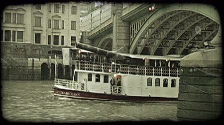 charakteristický : Large tour vessel boat, with conversing gentlement on bottom level, emerges from underneath a historic bridge as it continues on its path in a canal in London, England. Vintage stylized video clip.