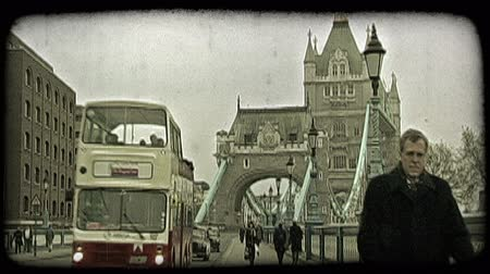 charakteristický : Everyday common people wearing warm clothing walk along street and walkway while cars and English bus rush by near main tower on famous historic Tower Bridge in London, England on an overcast day. Vintage stylized video clip.