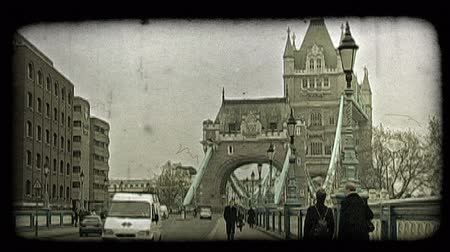 kültürlü : Everyday common people wearing warm clothing walk along street and walkway while cars and English bus rush by near main tower on famous historic Tower Bridge in London, England on an overcast day. Vintage stylized video clip.