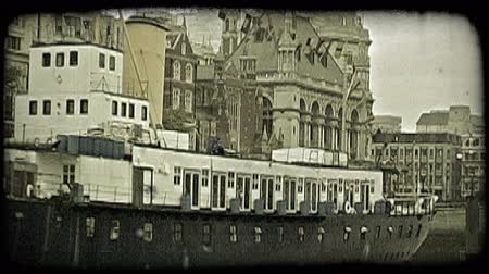 kültürlü : Large freight vessel boat with colorful national and international flags hanging from its top, as it rests at dock under and overcast sky near a historic building-filled street in London, England. Vintage stylized video clip. Stok Video