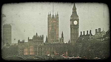 charakteristický : Wide shot of the famous Thames River next to Parliament, Big Ben and other well-known city buildings as lights begin to come on at dusk in London, England. Vintage stylized video clip.