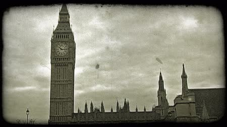 парламент : Famous Big Ben clock tower in London England on an overcast day, as a flag below waves in the wind. Vintage stylized video clip.
