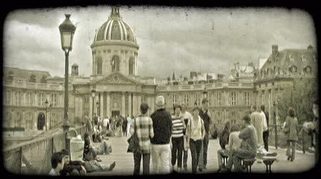 charakteristický : People walk and gather along busy walkway bridge in front of well-known, old, artistic, ornate French municipal building with dramatic cloud background in Paris France. Vintage stylized video clip. Dostupné videozáznamy