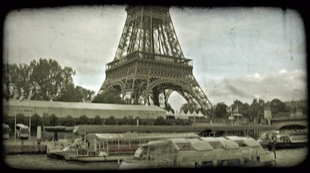 charakteristický : Lower part of Eiffel tower stands with trees surrounding it and clouds in background, behind the Sienne River where boats are at dock and others cross by in Paris, France. Vintage stylized video clip. Dostupné videozáznamy