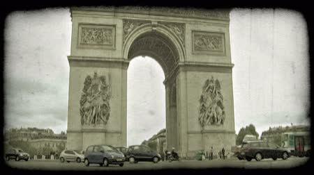 paříž : Cars and buses pass over the street circle that surrounds the famous, historic, ornate Arc de Triumph on a busy, cloudy day in Paris, France. Vintage stylized video clip. Dostupné videozáznamy