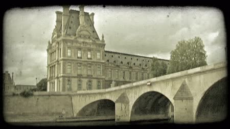 paříž : View of Paris, France historic building and bridge, with dramatic cloud background, from boat as it moves toward and then under an old bridge. Vintage stylized video clip. Dostupné videozáznamy