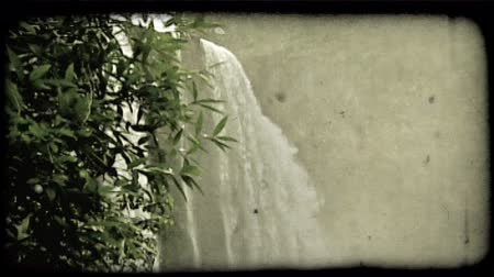 tahıllar : Zoom in on beautiful tall waterfall surrounded by tropical green plants in Hawaii. Vintage stylized video clip. Stok Video