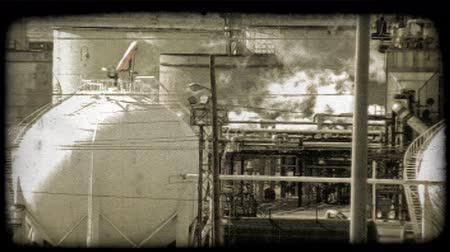 сжигать : A lock down shot of a Kuwaitee oil refinery with cars passing in the background. Vintage stylized video clip.