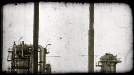 сжигать : A tilt down from the top of a smoke stack to the Kuwaitee oil refinary facilities. Vintage stylized video clip.