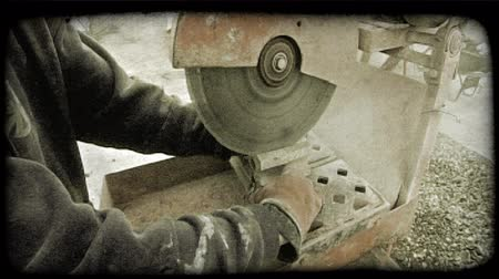 separado : Construction worker on site, wearing orange gloves, uses orange slicing blade machine to divide a large brick into two pieces. Vintage stylized video clip.