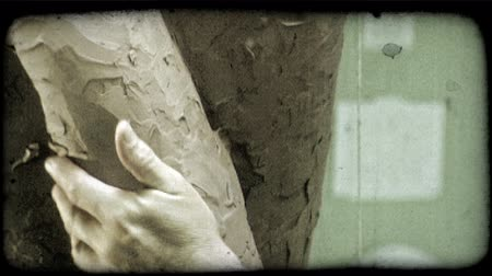 deneyimli : Close shot of professional sculptors expert hands as he places reddish clay piece onto side of large sculpture and blends it in by smearing it into its surroundings. Vintage stylized video clip. Stok Video