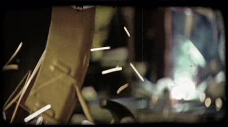 soldagem : Close up of man cutting metal with large bladed machine in foreground while man in background dressed in protective factory attire and helmet bends over metal work as he welds with a welding tube in a warehouse. Vintage stylized video clip.