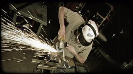 soldagem : Zoom in and out of young man from front in a warehouse work area as he splices metal apart with handheld blade machine, sending sparks all around it. Vintage stylized video clip.