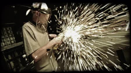 soldagem : Zoom in and out of young man from side in a warehouse work area as he splices metal apart with handheld blade machine, sending sparks all around it. Vintage stylized video clip. Vídeos