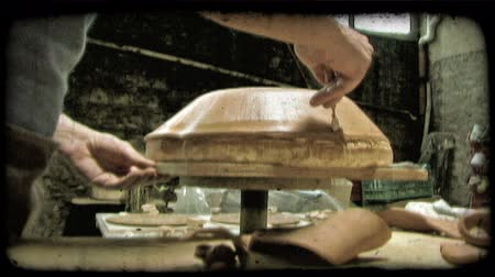 lití : A man cuts off the edges of clay around a mold in Italy. Vintage stylized video clip.