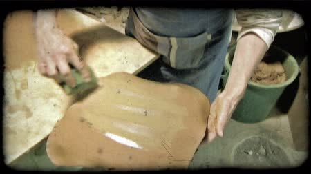 lití : A man forms clay tightly around a mold in Italy. Vintage stylized video clip.