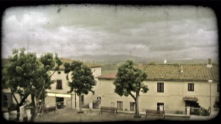 homes : A lock down wide shot of an Italian home or apartment buildings with storm clouds in the sky. Vintage stylized video clip.