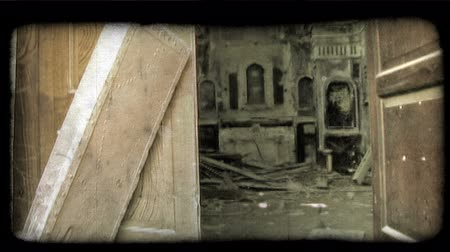 lebontották : Footage looking a doorway into an abandoned and deteriorating building, possibly a theater. There is a large pile of boards on the floor. Vintage stylized video clip.