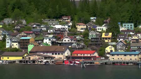 alasca : A sped-up tracking shot of Ketchikan buildings as seen from a passing ship. The houses are arranged in a multi-level way and some forest behind them is also visible as well as cars that drive between the houses. Captured on June 5, 2009. Vídeos